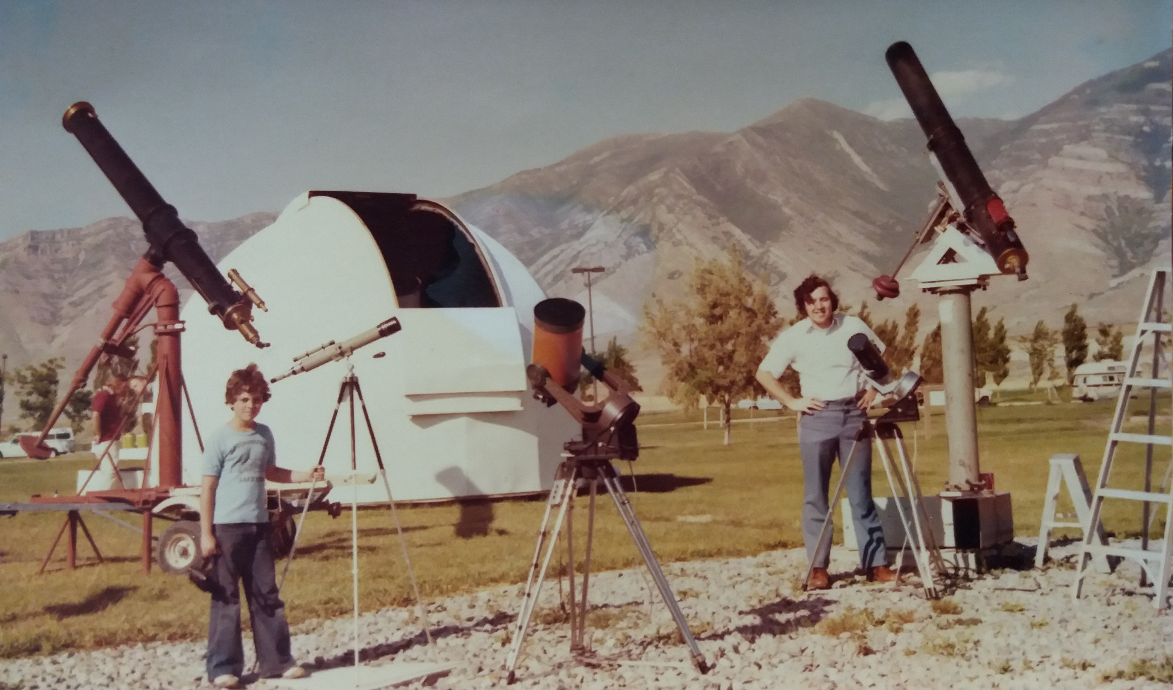 Large and small astronomical telescopes, standing near a white observatory dome. One adult to the right, on the left, a child with a telescope taller than him, frizzy brown hair, blue t-shirt, bell-bottom jeans and sneakers. Late afternoon sun, mountains in the background.