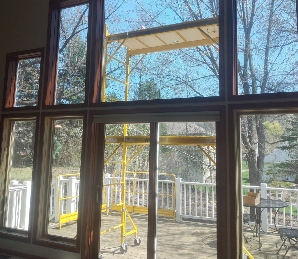 Large wall full of windows, from inside. Outside is a 12 foot tall yellow scaffold.